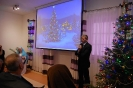 Sala muzykoterapii, pan Paweł Kacprzyk Prezes TOnOS zwraca się do Zgromadzonych, na ekranie wyświetlony obraz świątecznej choinki