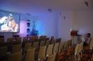 Sala muzykoterapii, pan Piotr w czasie ostatnich prób obsługi projektora wyświetla na ekranie obraz Świętej Rodziny