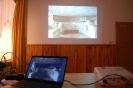 Świetlica w Domu Nadziei, pierwszy plan laptop i projektor stoją na blacie stołu, drugi plan fotografia z Ziemi Świętej wyświetlona na ścianie