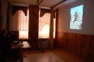 Świetlica w Domu Nadziei, po lewej stronie przy stoliku siedzą ks. Antoni i s. Pia, omawiają fotografie wyświetlone na ścianie po prawej stronie