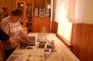 Świetlica w Domu Nadziei, pani Grażynka stoi przy stole z pamiątkami i  ogląda album o Ziemi Świętej