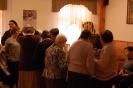 Świetlica w Domu Nadziei, uczestnicy spotkania przy stole z pamiątkami oglądają menorę, przymierzają jarmułkę, zadają pytania