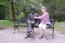 Nałęczów, Park Zdrojowy, Pani Dagmara siedzi na ławeczce i ogląda figurę Bolesława Prusa, również siedzącej na ławeczce, naturalnej wielkości odlanej z brązu