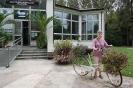Nałęczów, Park Zdrojowy, Pani Dagmarka ogląda kwietnik z roweru stojący przed budynkiem Palmiarni