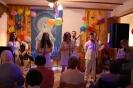 Świetlica w Domu Nadziei, pierwszy plan publiczność, drugi plan Pani Paulina przedstawia Kapelę Styrta, trzeci plan Członkowie Kapeli ubrani w białe płócienne ludowe stroje stoją na scenie