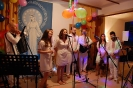 Świetlica w Domu Nadziei przybrana balonami i bibułą, występ Kapeli Styrta, pierwszy plan Kobiety i Mężczyźni ubrani w białe płócienne stroje ludowe
